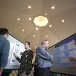 Students and faculty members talk between bulletin boards featuring posters.