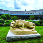 A Penn State Nittany Lion statue is positioned in front of the Penn State Health St. Joseph Medical Center on a grassy lawn lined with trees.