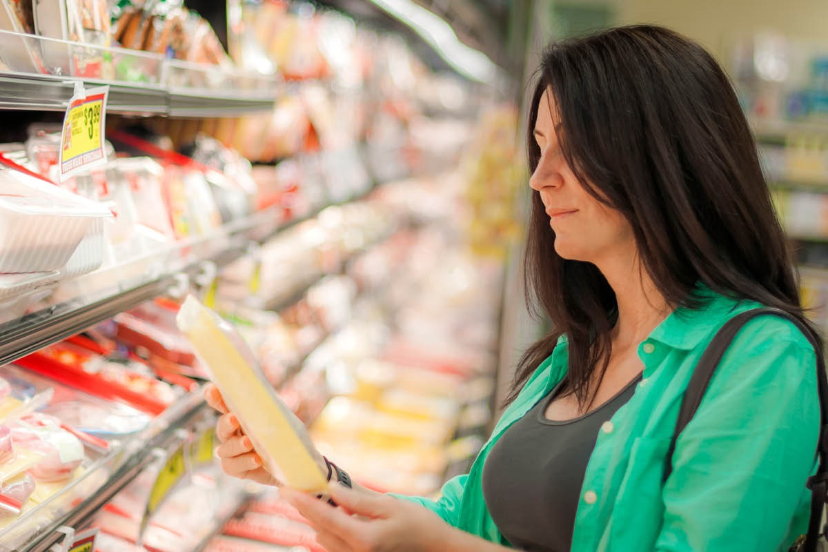 A woman looks at a package of meat at a grocery store meat counter.