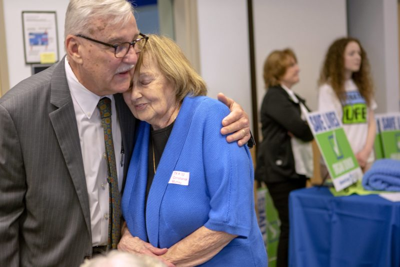 "Dr. John Pennock, wearing a sport jacket and tie, wraps an arm around Constance Murray. Both are standing in a room surrounded by other people with signs and T-shirts that say ""Save Lives."""
