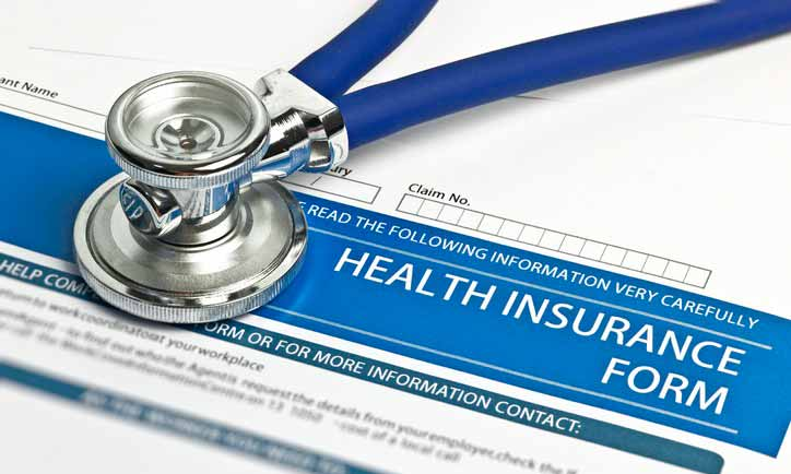 A close-up of a stethoscope sits on a blank health insurance form.