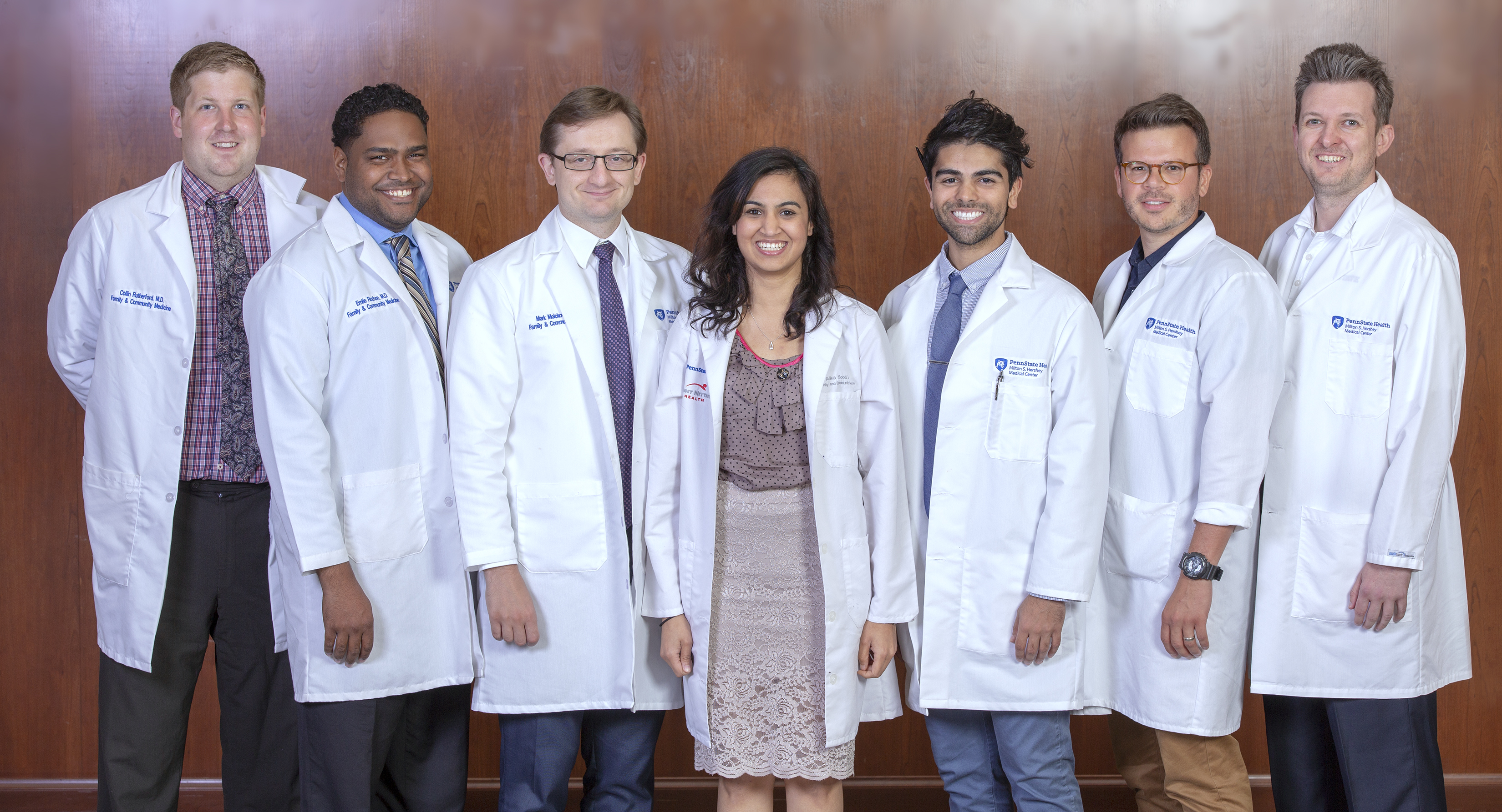 Six men and one woman wearing white lab coats with the Hershey Medical Center logo and their names on them stand in a row and smile. The men are wearing shirts and ties, and the woman is wearing a skirt and top. The wall behind them is made of wood paneling.