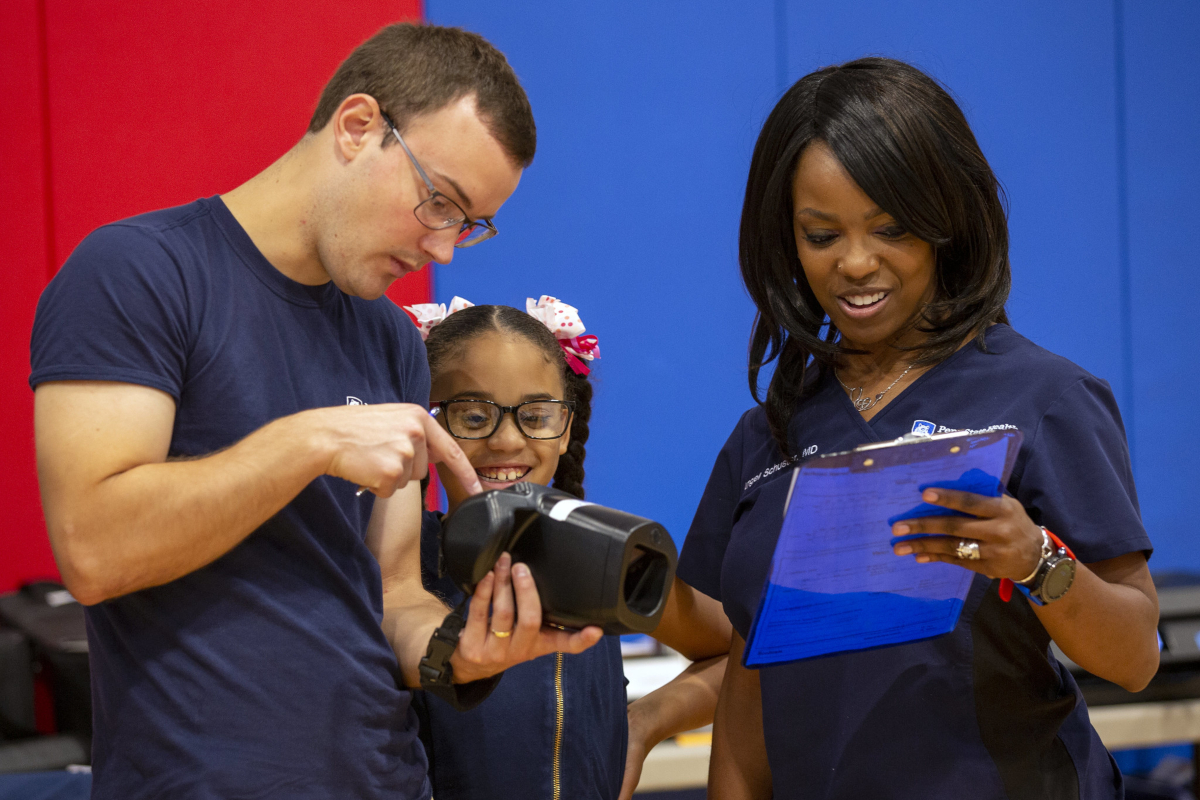 A man holds a piece of vision screening equipment, pointing to it, as a young girl looks on. A woman stands on the other side of the girl, holding and looking at a clipboard.