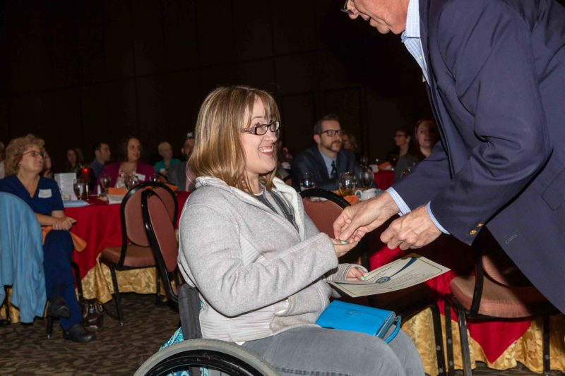 Megan Patrick, wearing a sweatshirt and jeans, smiles at a man in a sport coat who is placing something in her hand. In her other hand, she holds a certificate.