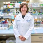 Dr. Leslie Parent, wearing a lab coat, stands in a lab. Behind her is a desk and shelves covered with bottles and equipment.