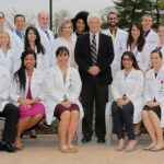Dr. John Repke, wearing a suit, poses outdoors with 26 residents - some seated, some standing -- all of whom wear white clinical coats.