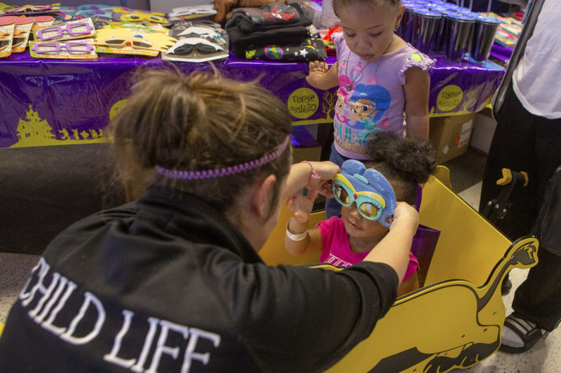Child Life Assistant Tiffaney Horner places special glasses on the face of 2-year-old Ava Lawson as her sister Aurora, 3, looks on. Ava is seated in a toy car. In the near background is a table with sunglasses, shirts, cups and other merchandise on it.