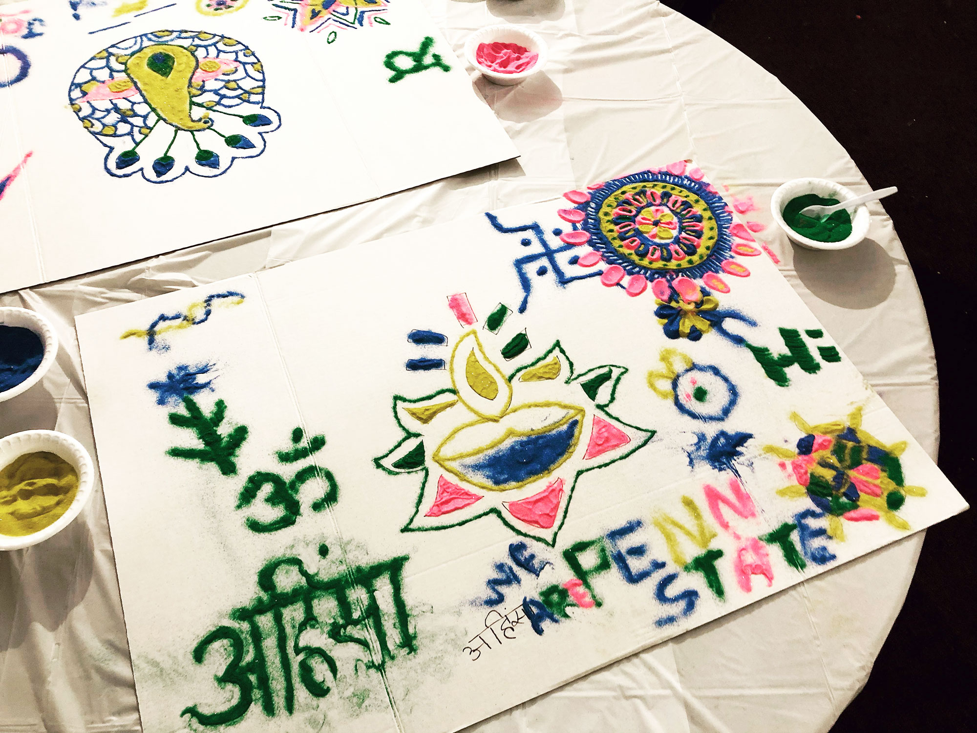 A piece of paper is covered in brightly colored drawings depicting flowers and geometric patterns, as well as the words We Are Penn State and writing in another language.