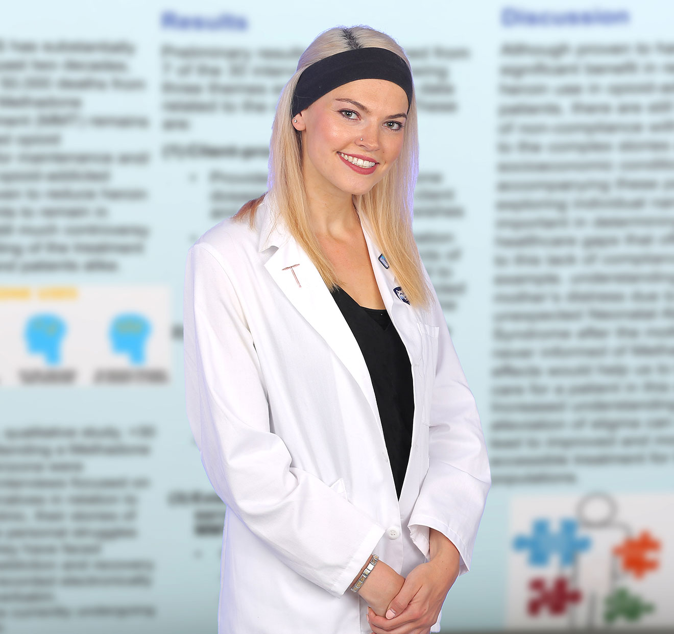 A medical student wearing a medical coat is pictured with an out-of-focus scholarly poster of hers visible in the background.