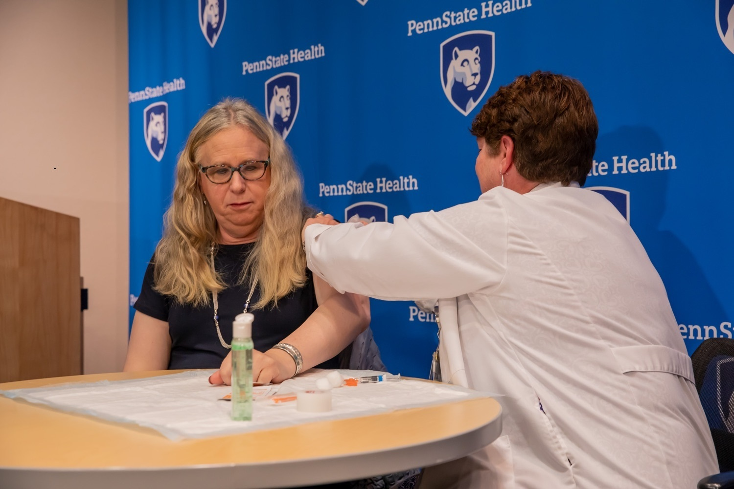 Dr. Rachel Levine, left, sits at a table with Lori Bechtel, nurse manager for Employee Health and Employee Safety as Bechtel gives her a flu shot. Levine has long, wavy hair and is wearing glasses and a dress. Bechtel has short hair and is wearing a white lab coat. Hand sanitizer and a syringe are on the table. Behind them is a banner with the Penn State Health logo on it and a podium.
