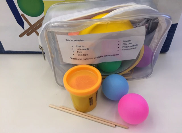 A small plastic bag is seen containing Play-Doh, craft sticks, tape, small balls and more.