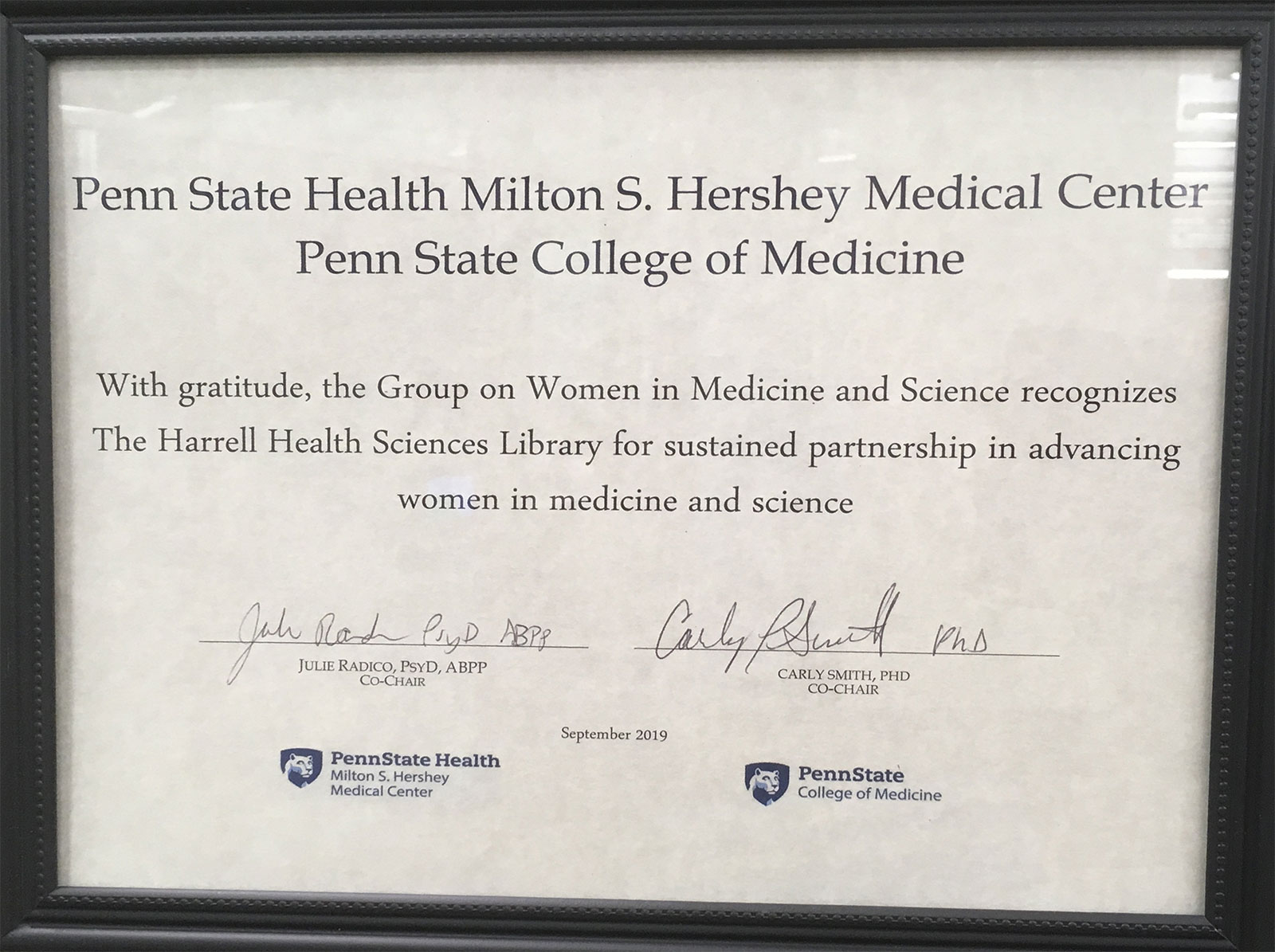 A framed certificate honoring Harrell Health Sciences Library is seen signed by leaders of the Group on Women in Medicine and Science.