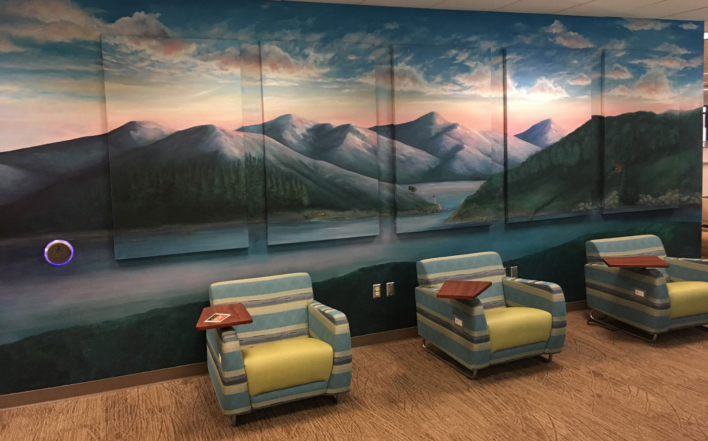 A multi-panel mural depicting mountains with an ocean in front of them and a sky above them is seen in a room with large, comfortable chairs in front of it.