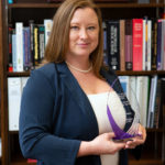A professional photo of Jennifer Nyland, PhD, shows her holding an award as a Woman to Watch in STEM. She is standing in her office with books and a framed degree in the background.