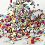 A few hundred pills of various types are dumped onto a plain space.