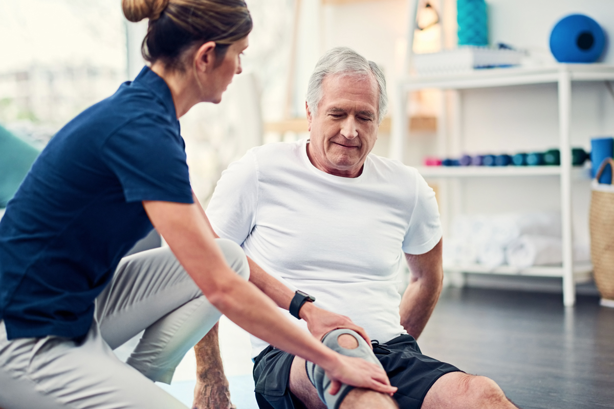 A female physical therapist kneels down as she places her hands on both sides of a man's knee. He is seated on the floor, with a brace on the knee. Various physical therapy equipment is in the background, out of focus.