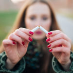 A woman stands outdors, facing the camera. She holds up a cigarette as she breaks it in half in front of the camera.