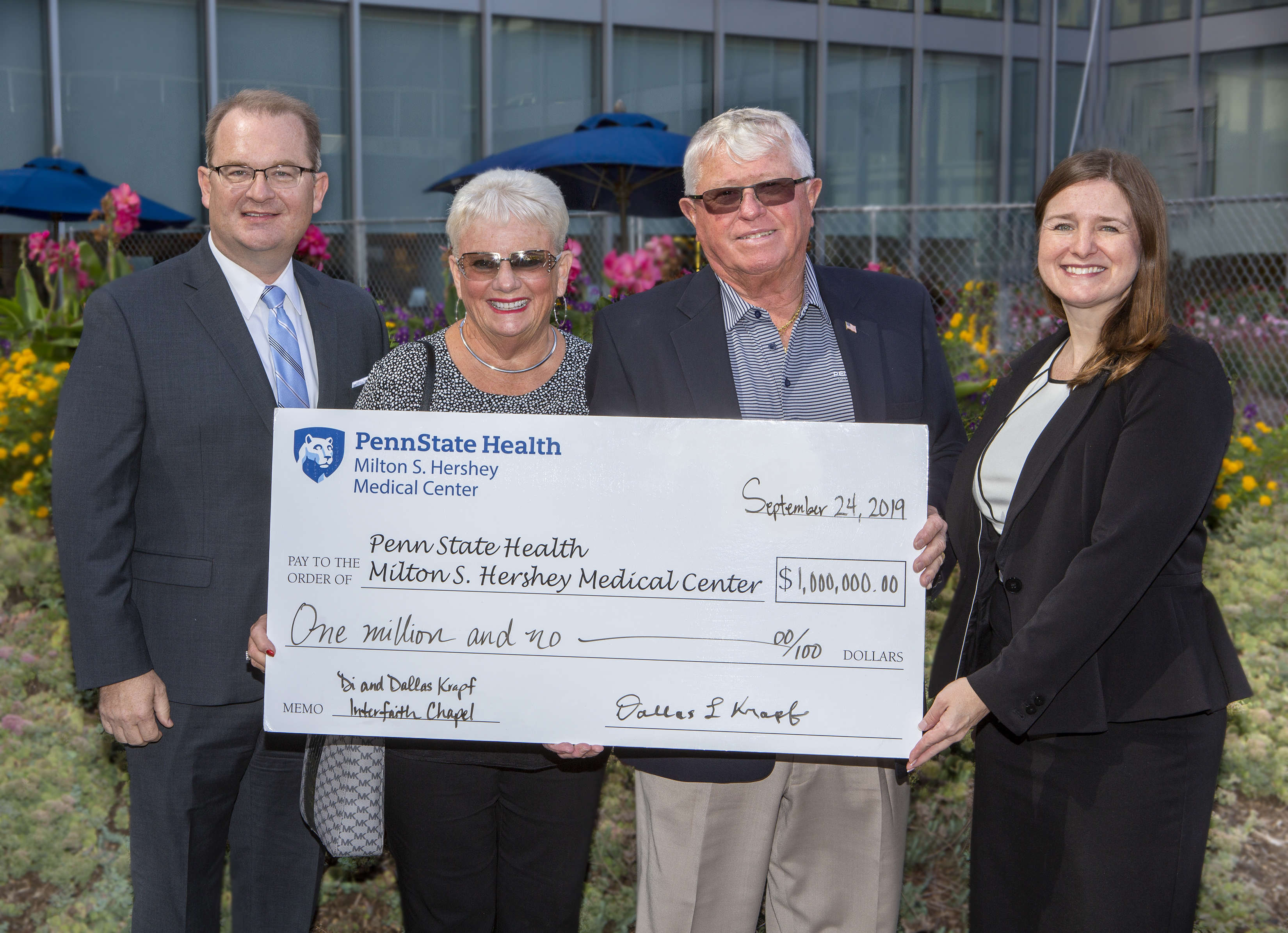 Four people – two men and two women – pose outside for a photo holding an oversized check made out to Penn State Health Milton S. Hershey Medical Center, in the amount of $1 million. It's signed by Dallas Krapf. A building with windows is in the background, as are bushes and flowers.