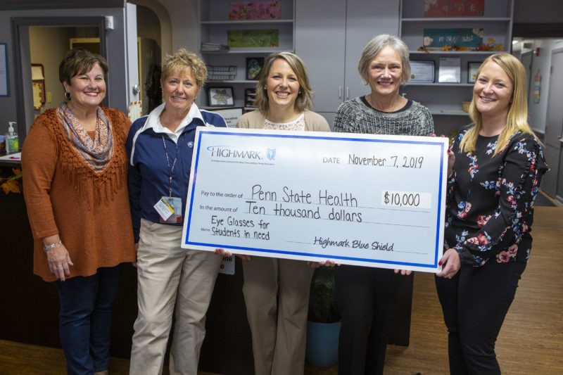 Five women pose with an oversized check in the amount of $10,000, made out from Highmark to Penn State Health. The Memo line reads: Eye glasses for students in need. A desk and office shelves are in the background.