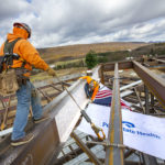 Two construction workers guide a steel beam into place on the top of a steel frame structure