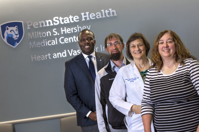 Four people are stand in a row in front of a sign for Penn State Health Milton S. Hershey Medical Center Heart and Vascular Institute.