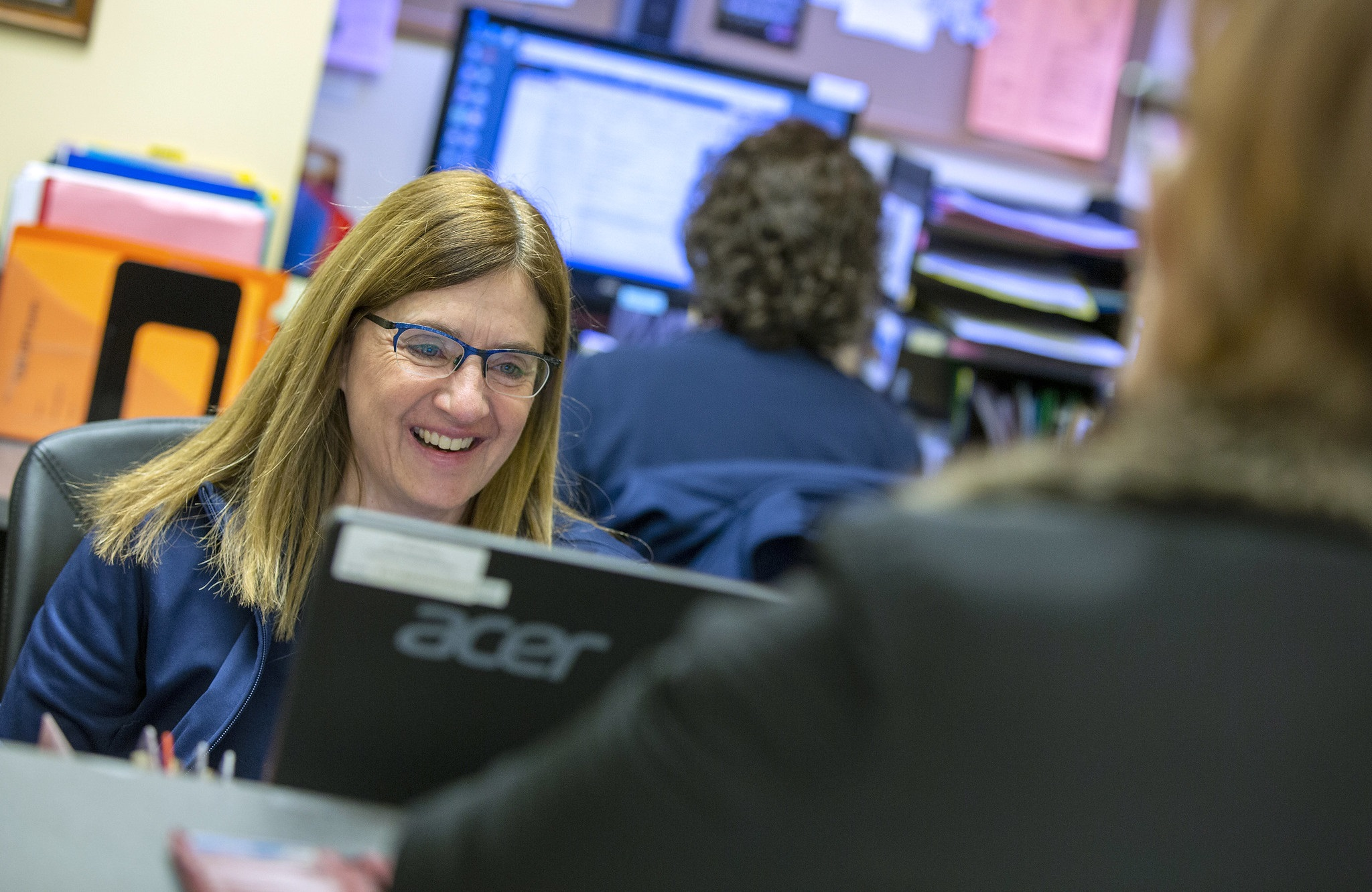 Medical office associate Laura Bjanes smiles as she looks at her computer monitor. She has shoulder-length hair, glasses and is wearing a polo shirt. In front of her a woman is seeing from behind standing at the counter. Another woman employee is behind Laura working at a computer.