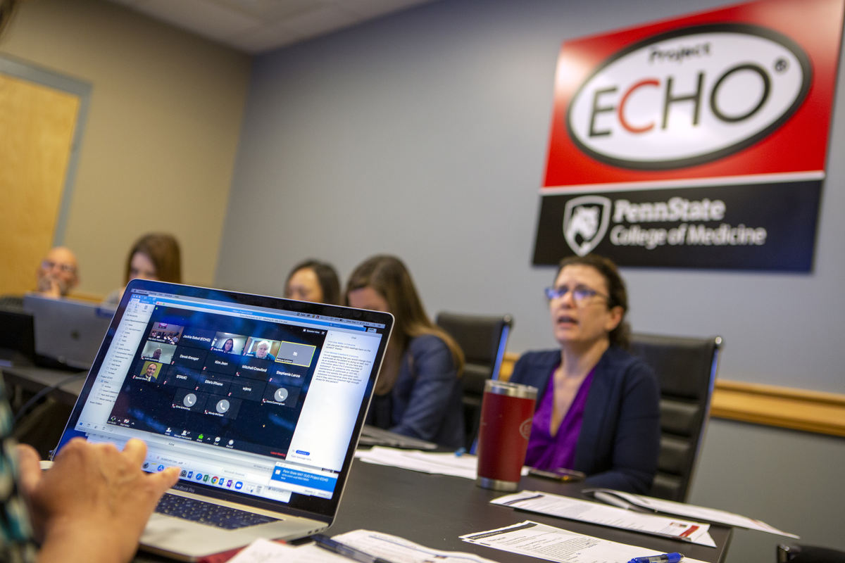 Several people sit around a conference table, on which there are papers, pens and computers. A sign on the wall bears the Project Echo and Penn State College of Medicine logos.