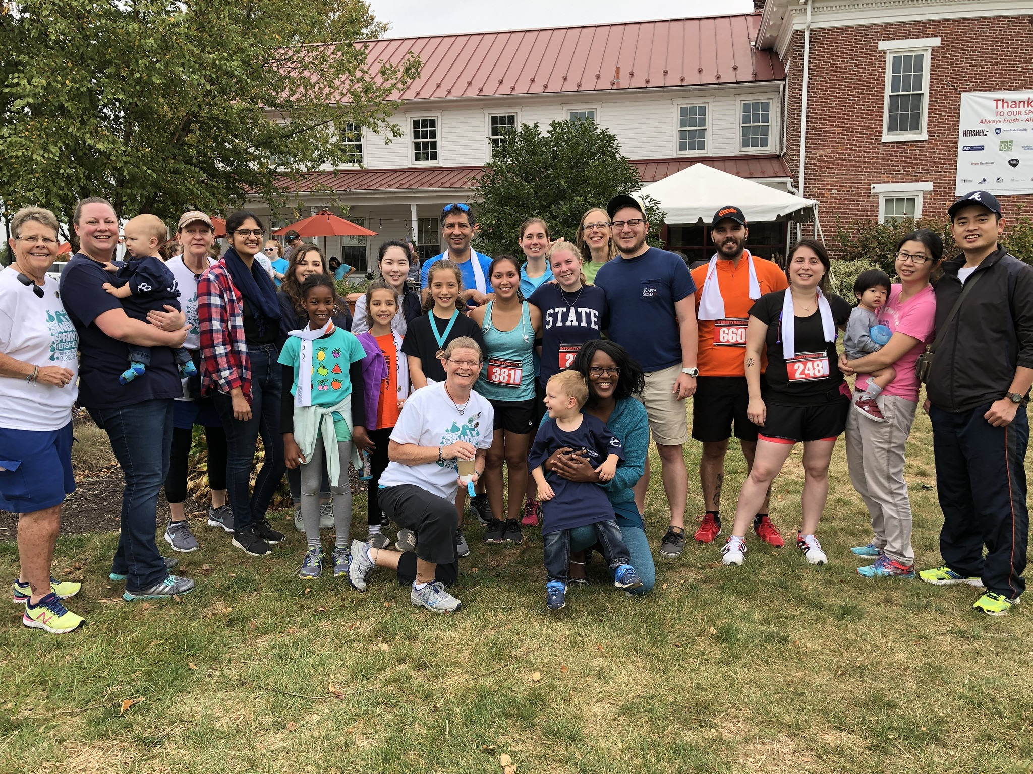About a dozen participants from Penn State Health's first annual Sandy Sprint pose on the lawn in front of a large brick house. In the forefront, ovarian cancer patient Michelle Kirscht, dressed in a T-shirt and capris, kneels next to her cancer surgeon, Dr. Rebecca Phaeton, gynecologic oncologist at Penn State Health Milton S. Hershey Medical Center, who is holding a young boy in her lap.