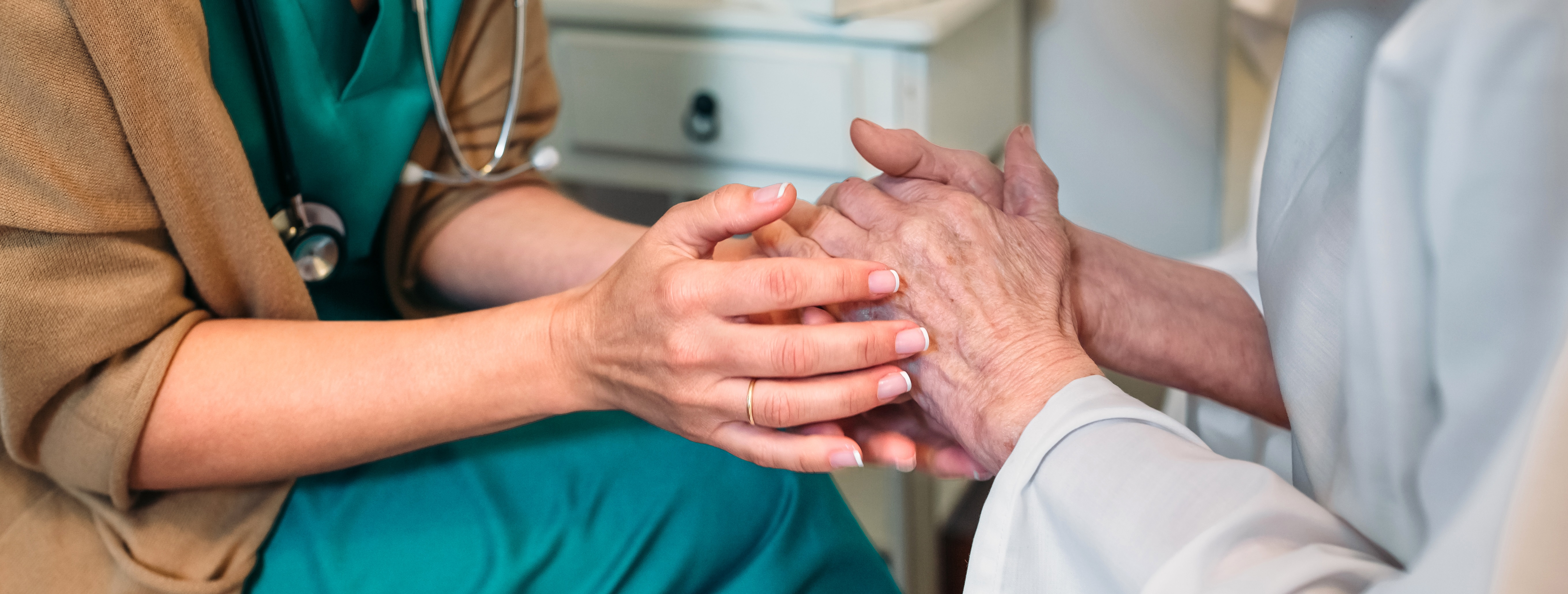 Two pairs of hands intertwine. One pair belongs to someone wearing a stethoscope and scrubs. The other belongs to someone in a white gown.
