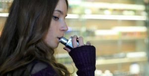 A teenage girl is pictured smoking an electronic cigarette. A blurred image of a vape bar is in the background