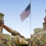 U.S. soldiers are shown from behind saluting a U.S. flag.