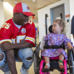 LeSean McCoy, wearing a Kansas City Chiefs uniform and hat, kneels down to talk with a young girl in a wheelchair. She looks back at him.