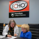 Two women sit at a table working with a Project ECHO logo on the wall behind them.