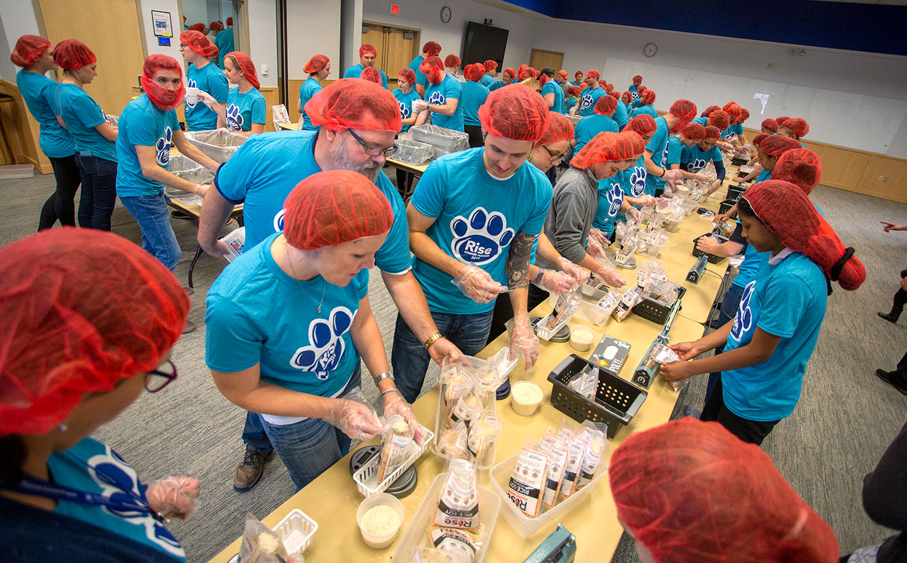 A group of students wearing matching T-shirts and hairnets is seen packing food items in a large room.