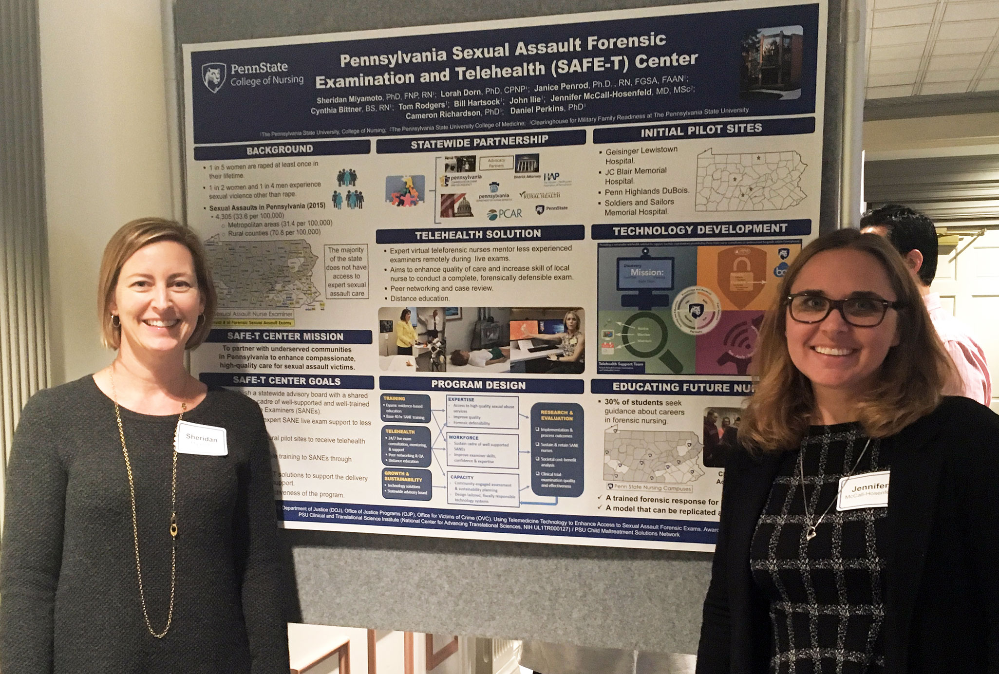 Two women are seen smiling, standing in front of an academic poster.