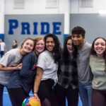 "Six high school students – five female and one male – pose for a group photo with arms around each other. They're in a school gym, where a wall with the word ""PRIDE"" is in the background."