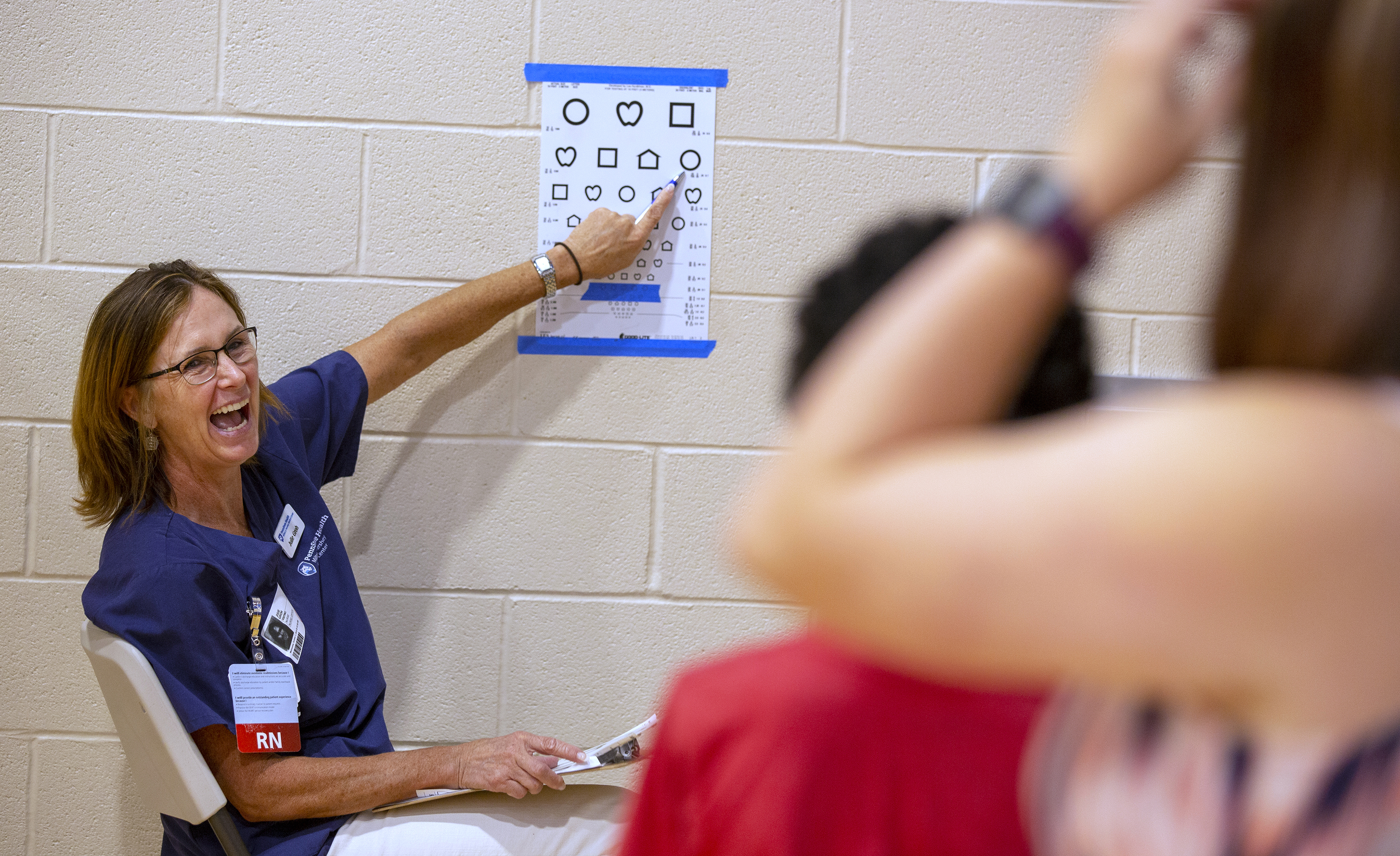 "Julie Groh smiles as she points to a shape on an eye chart. She has shoulder-length hair and is wearing glasses, scrubs and an ID badge with ""RN"" on it. Two children are in the foreground out of focus."