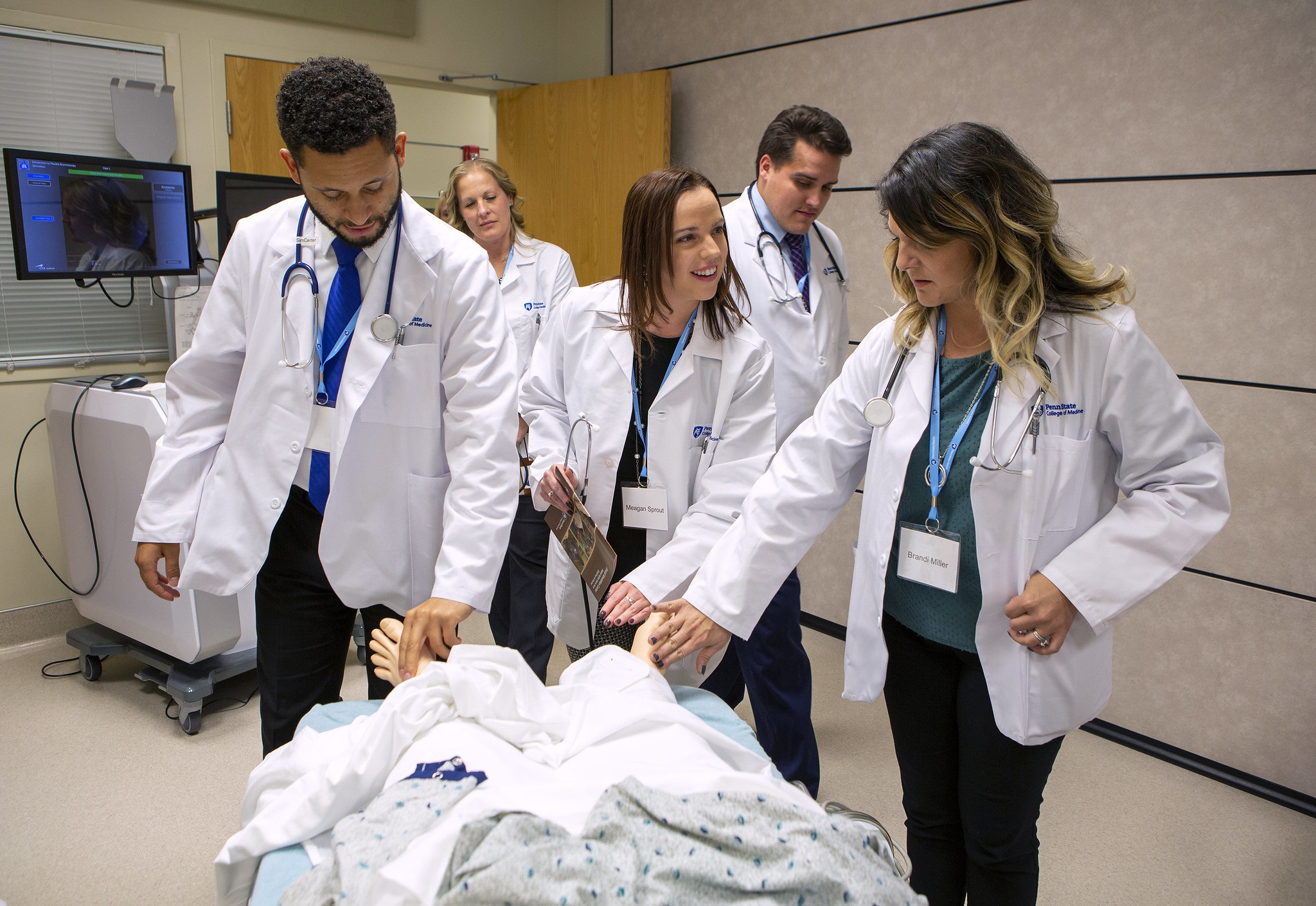 A man and two women touch the feet of a mannequin that is lying on a table. Behind them a woman and man stand. All five are wearing white lab coats. Behind them is a cart with two monitors and a door.