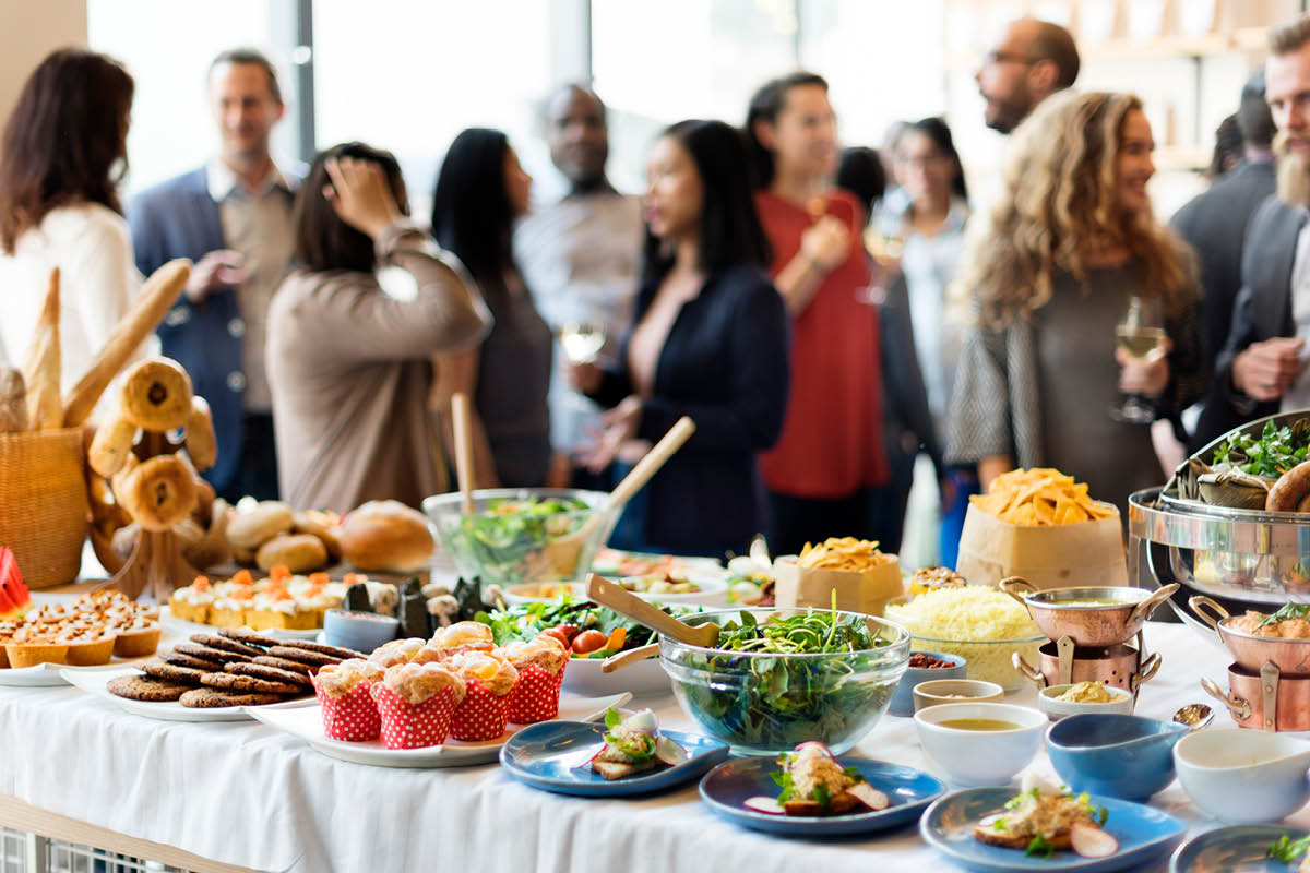 A table with plates and bowls of food is in the foreground. It includes a salad, cookies, muffins, bread and various hors d'oeuvres. In the background, several people are standing and talking, some of them holding drinks.