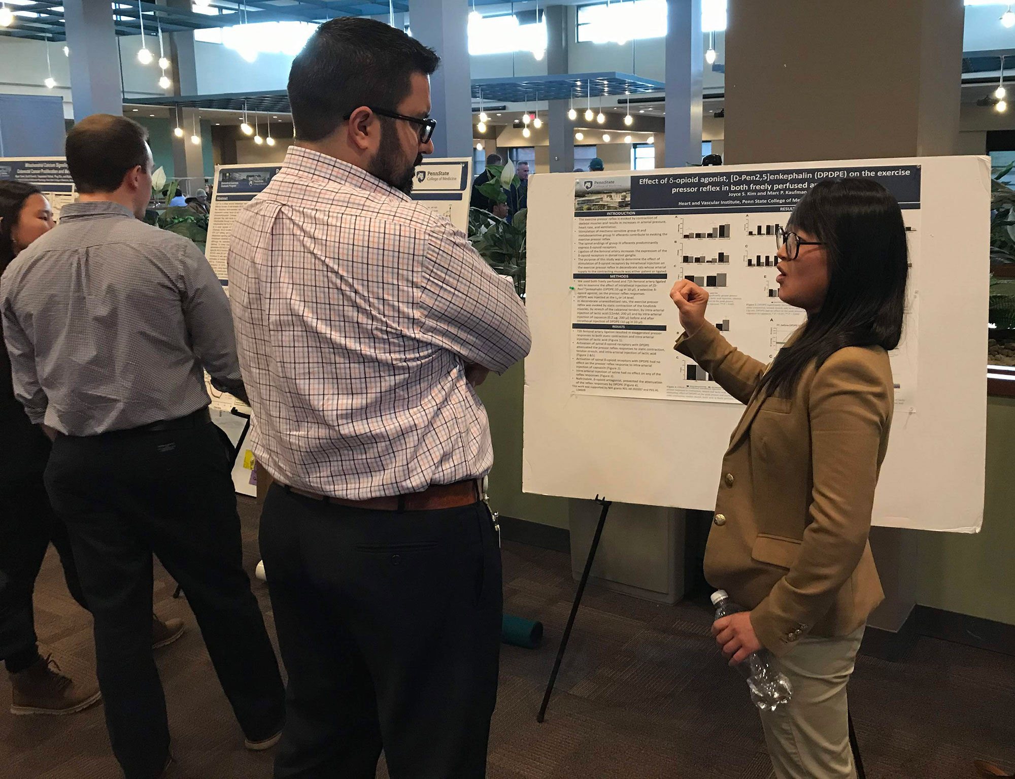Two people stand in front of an academic poster, talking.