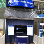 The Penn State Health front porch is a wooden stage with a porch with shingles rising behind it, lined by a railing.