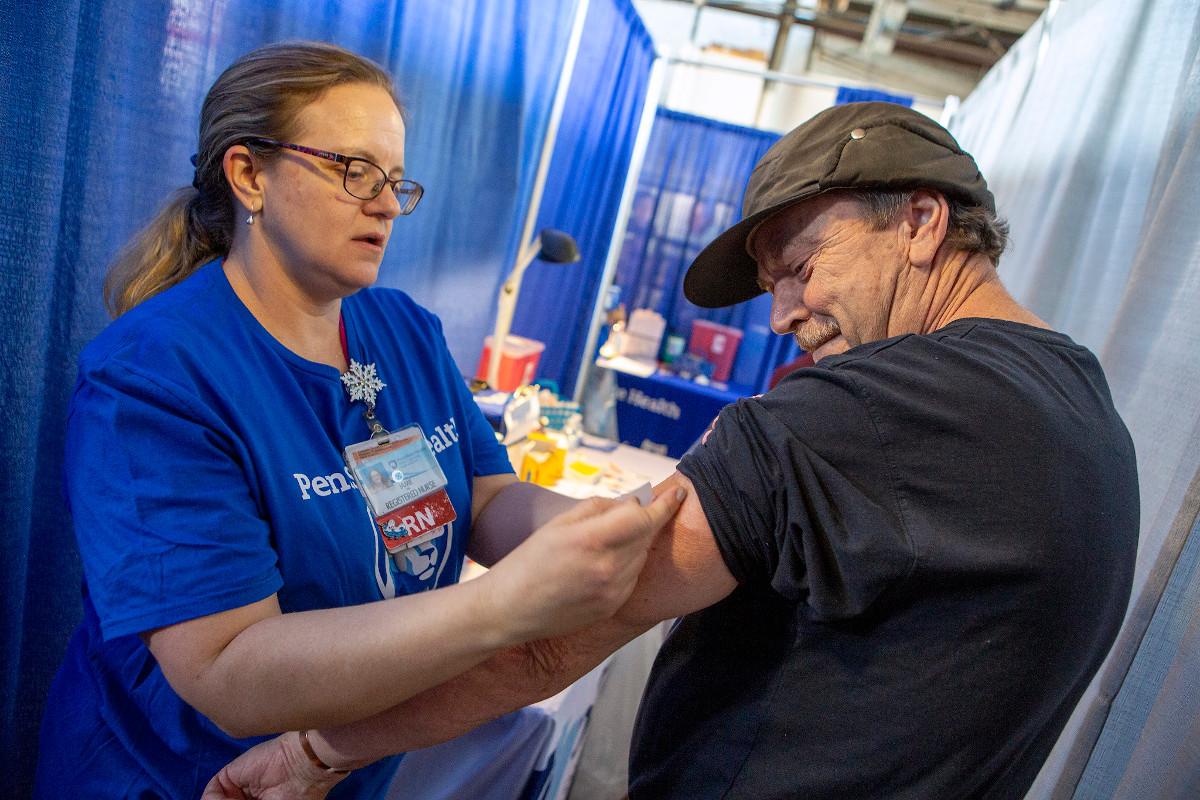 A nurse gives a man a flu shot in his arm