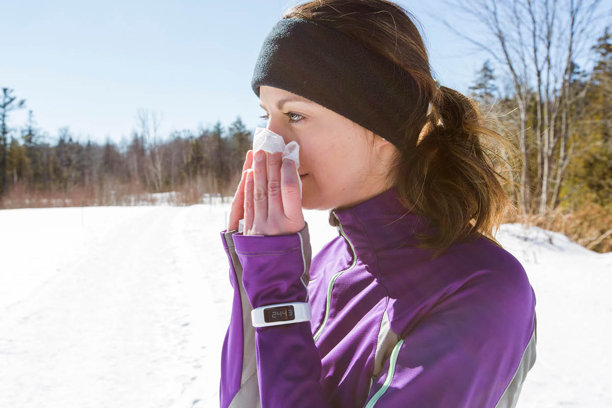 A woman stands outside in winter, wearing workout clothes including a jacket and headband. She holds a tissue up to her nose. Snow is on the ground and trees are in the background.