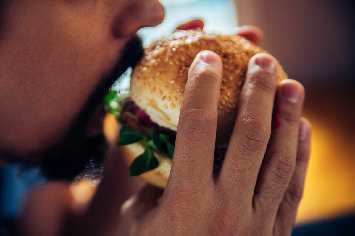 A close-up of a man with a short beard and mustache holding a burger on a bun, about to take a bite out of it. He holds the burger with both hands.