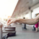 An outstretched hand holds a cigarette butt as its remnants are snuffed in an ashtray, which is mounted to a pole outdoors. Vehicles and a building are in the background, slightly out of focus.