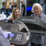A young woman smiles as an older woman wearing a nasal cannula and a checkered dress and standing on a treadmill. They are in the Health and Wellness Center on the Hershey Medical Center campus. Three people are standing behind them out of focus.