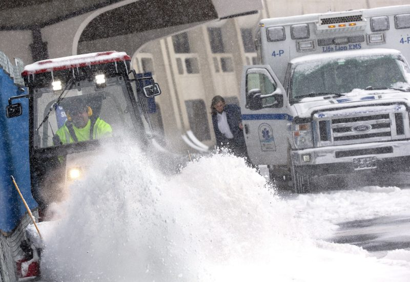 A plow flings a pile of snow into the air. Behind it, someone steps out of an ambulance.
