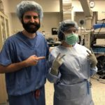 Dr. Eric Pauli poses with registered nurse Kiersten Marie in the operating room. Marie wears a surgical gown, gloves, mask, hair net and glasses. Pauli, who has a beard and moustache, wears scrubs and points his index finger toward Marie. Operating equipment is in the background.
