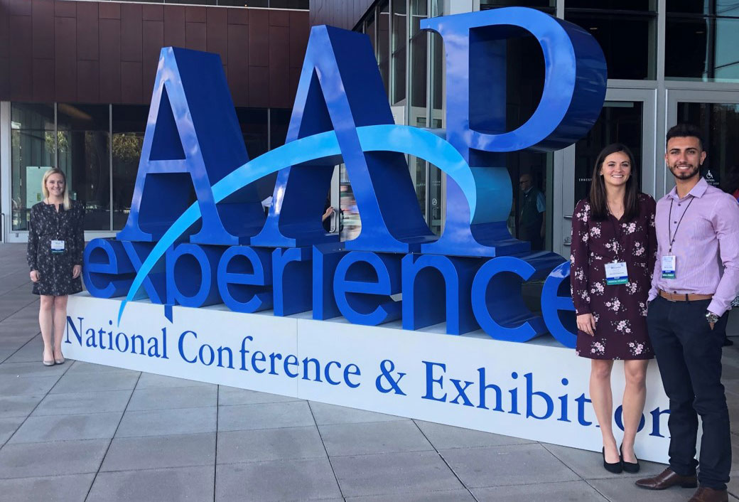 Three people stand next to a large sign that says AAP experience, wearing professional attire.