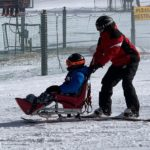 An instructor pushes an adaptive skier in a wheelchair down a slope at Roundtop Mountain Resort. Both are wearing ski jackets, ski pants and helmets. Two people stand in the background, and one person lies on the ground.